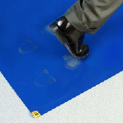 worker stepping on a peel off tacky mat