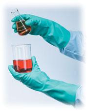 scientist wearing chemical gloves when combining beakers of chemicals